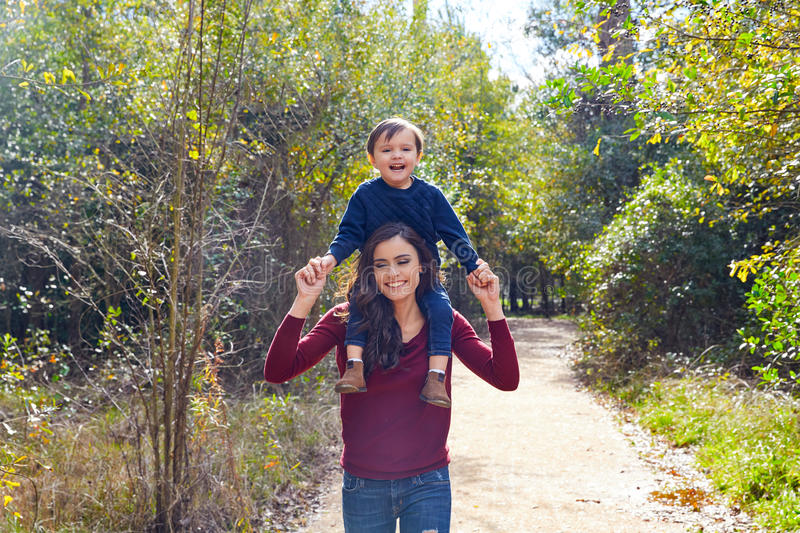 Kid boy sit on mother shoulders walking park stock photography