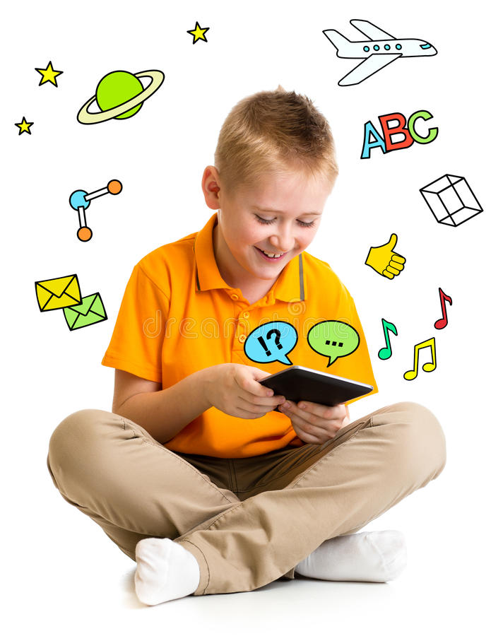 Kid boy sitting with tablet computer and learning or playing. With great interest royalty free stock image