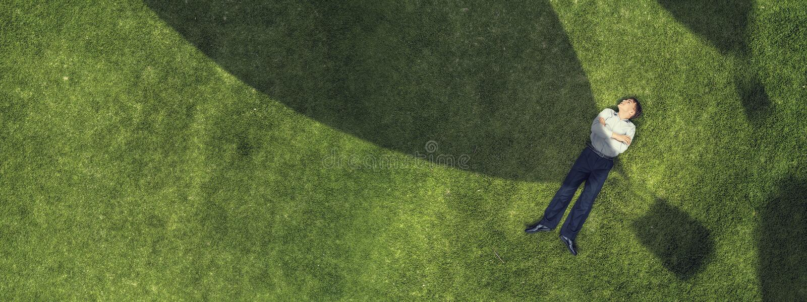 Kid relaxing on grass royalty free stock image