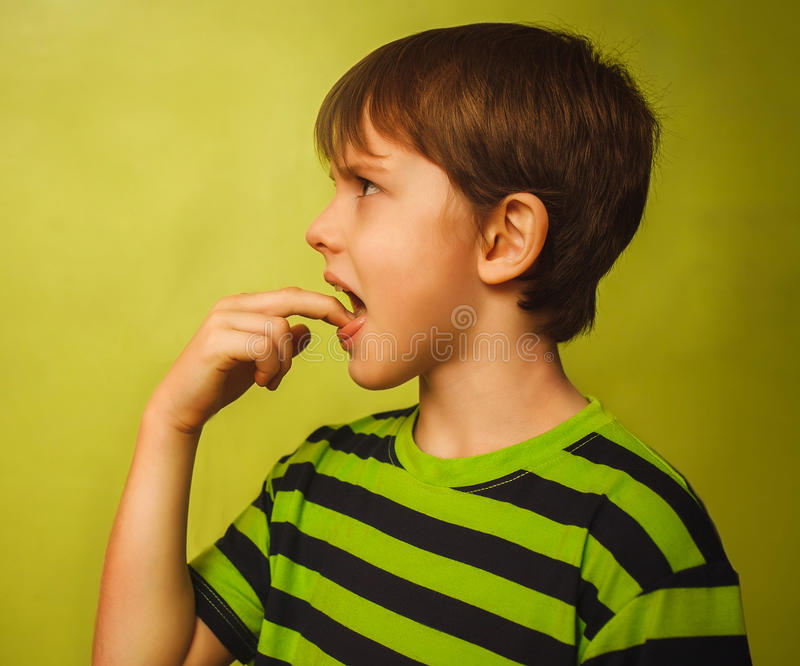 Kid boy teenager baby poisoning vomiting belching,. Anorexia fingers in mouth burps on green background gray stock image