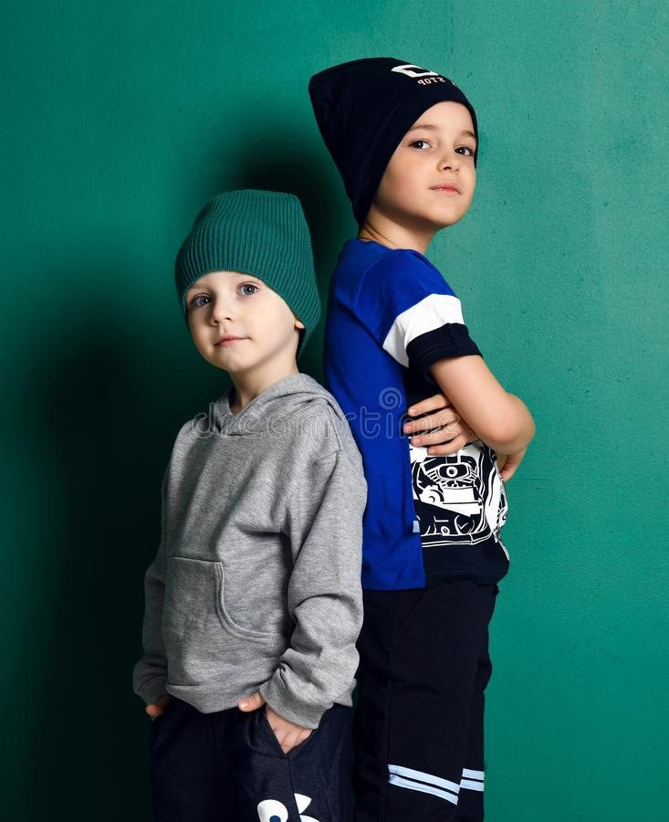 Kid boy and teenager in modern sportswear knitted hats, pants, hoody and t-shirt cool posing back to back on green stock image