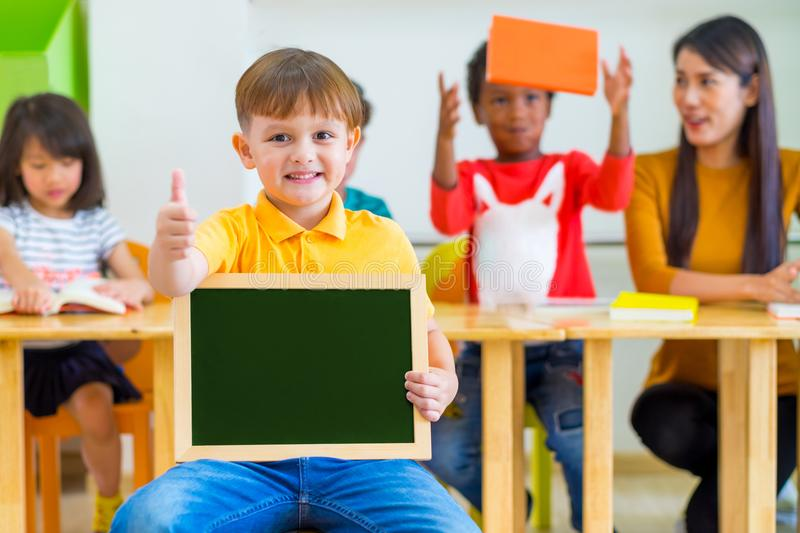 Kid boy thumbs up and holding blackboard with back to school word with diversity friends and teacher at background,Kindergarten s royalty free stock photography