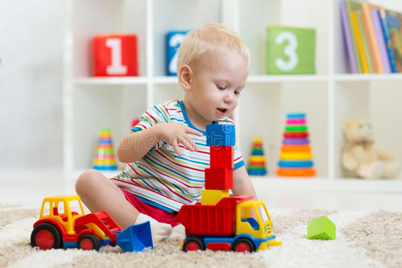 Kid boy toddler playing with toy car in nursery stock photos