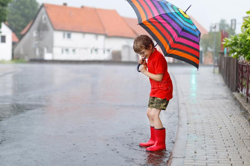 Kid boy wearing red rain boots and walking with umbrella. Kid boy wearing red rain boots and walking with colorful umbrella on city street. Child with glasses on royalty free stock images