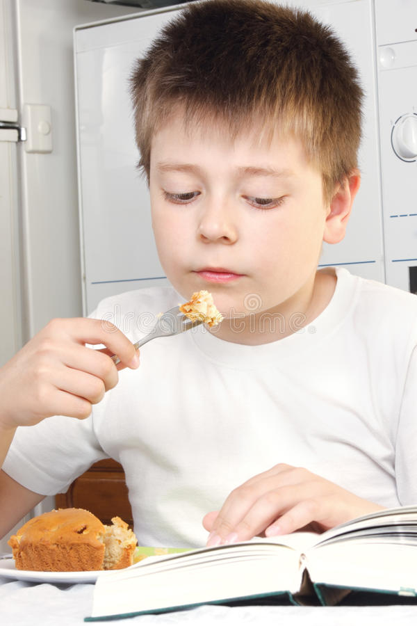 Kid at breakfast with book royalty free stock image