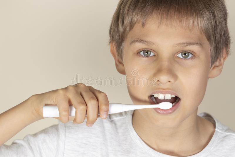 Kid brushing teeth with white electric toothbrush royalty free stock photo