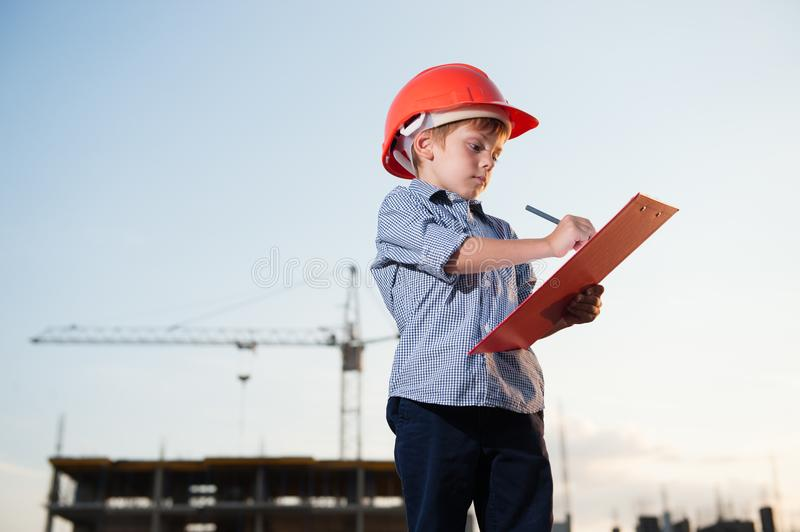 Kid builder wearing orange helmet takes notes on building site background stock photography