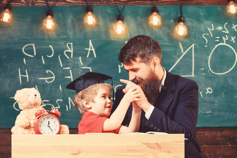 Kid cheerful distracting while studying, attention deficit. Father with beard, teacher teaches son, little boy. Teacher stock images