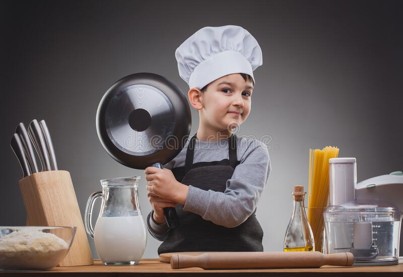 Boy Chef Cooking on a gray background. royalty free stock images