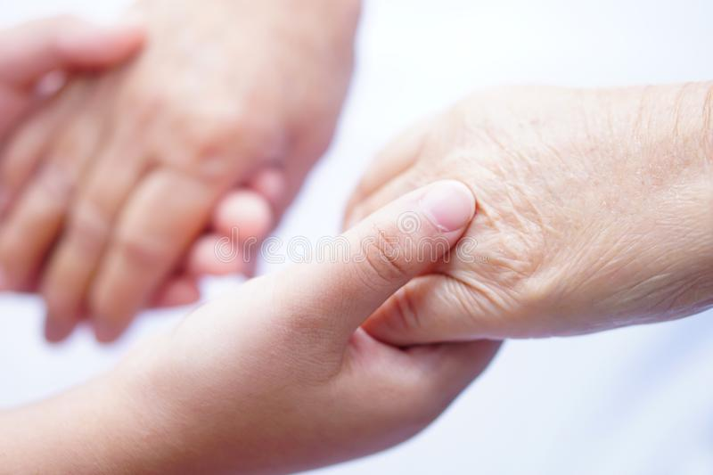 Kid Children holding hand Asian senior or elderly old lady patient with love, care, encourage and empathy. stock image