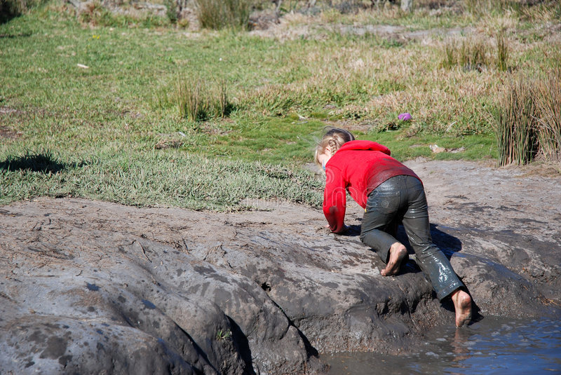 Kid climbing muddy pool. A little caucasian girl child in wet clothes having great fun by climbing out of a muddy dirty pool on an adventure playground outdoors stock photos