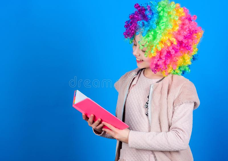 Kid colorful curly wig artificial hair clown style hold book. Reading jokes. Time to have fun. Circus school. Study hard. Ridiculous story. Reading funny book royalty free stock photo