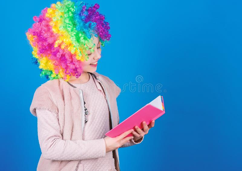 Kid colorful curly wig artificial hair clown style hold book. Reading jokes. Time to have fun. Circus school. Study hard. Ridiculous story. Reading funny book stock image