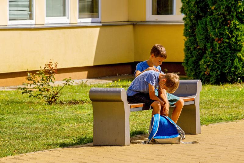 Kid comforting consoling upset sad boy in school yard royalty free stock image