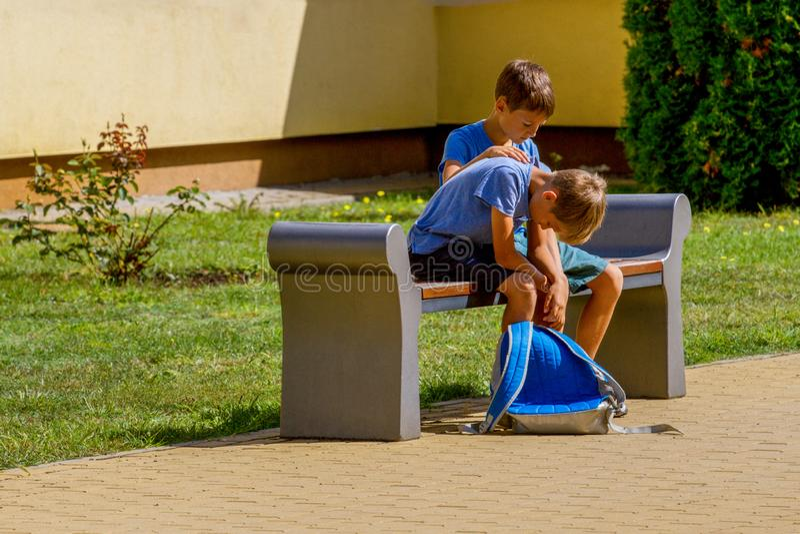 Kid comforting consoling upset sad boy in school yard royalty free stock photography