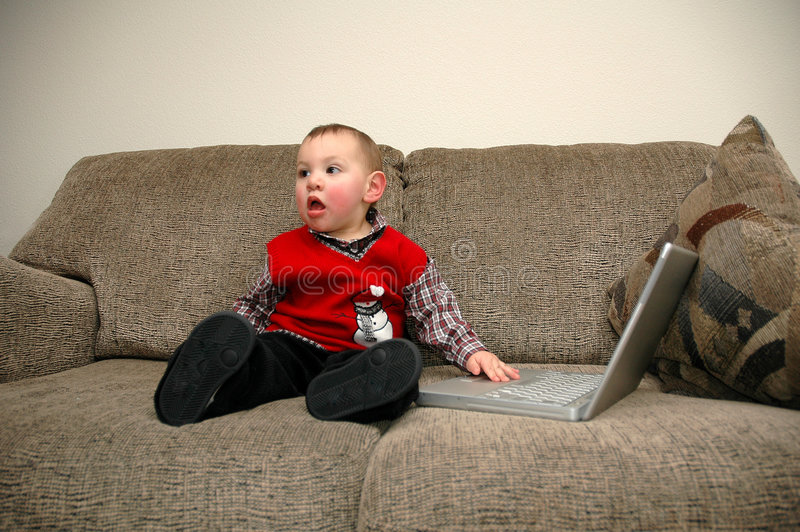 Kid and computer. Kid playing with computer royalty free stock photography