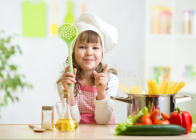 Kid cook makes healthy vegetables meal in the. Kid girl cook makes healthy vegetables meal in the kitchen stock images
