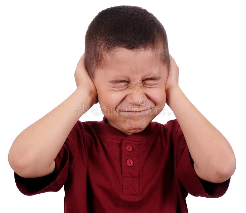 Kid covering ears. Eight year old boy holding his ears from loud noise, isolated on pure white background royalty free stock photography