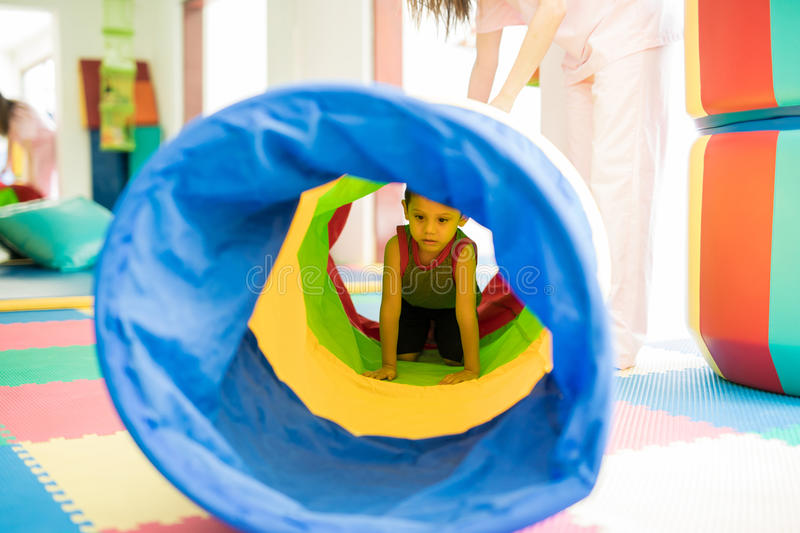 Kid crawling through a tunnel. Little kid playing and crawling through a tunnel in an obstacle course at a children physical therapy center stock photo
