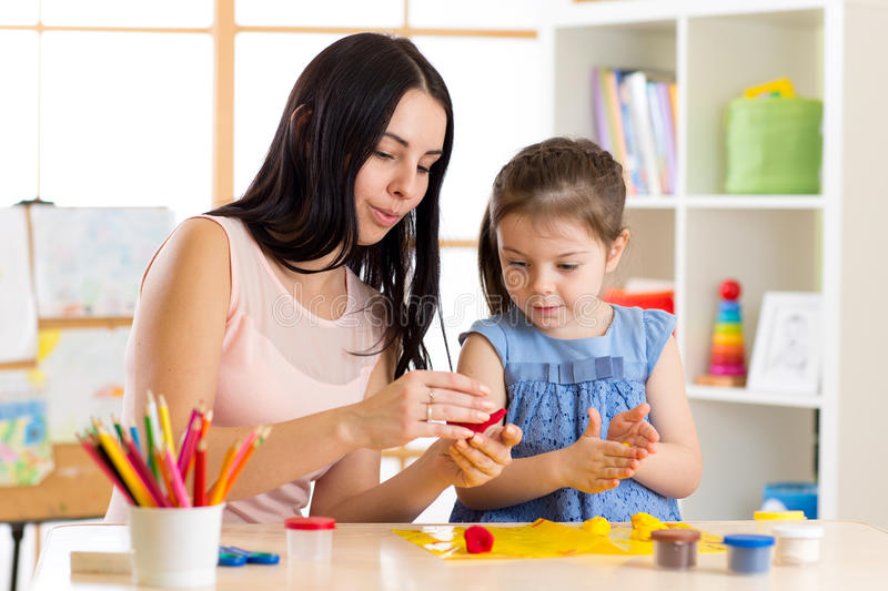 Kid creativity. Child girl with her mother sculpting from play clay stock photo