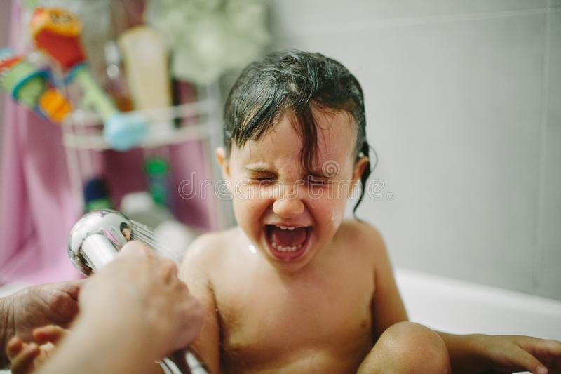 Kid crying while taking a bath stock photography