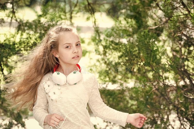 Kid dance to music in summer park. Small child enjoy music in headphones outdoor. Girl dancer with long flying hair. Melody sound and mp3. Summer fun and joy royalty free stock images