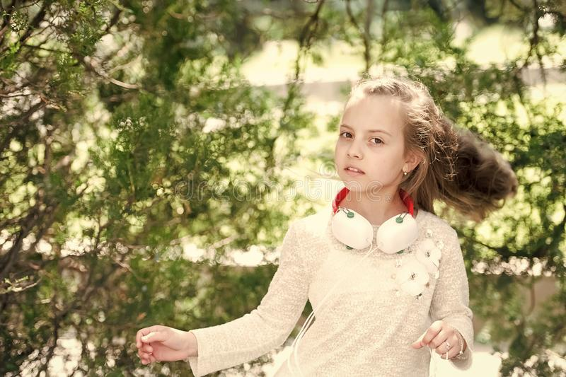 Kid dancer with long flying hair. Girl dance to music in summer park. Small child enjoy music in headphones outdoor. Melody sound and mp3. Summer fun and joy stock photos