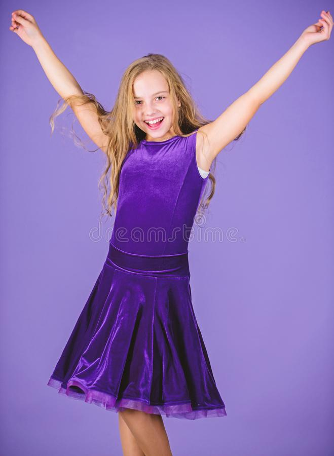 Kid dancer satisfied with concert outfit. Ballroom fashion. Girl child wear velvet violet dress. Clothes for ballroom. Dance. Kid fashionable dress looks stock photo