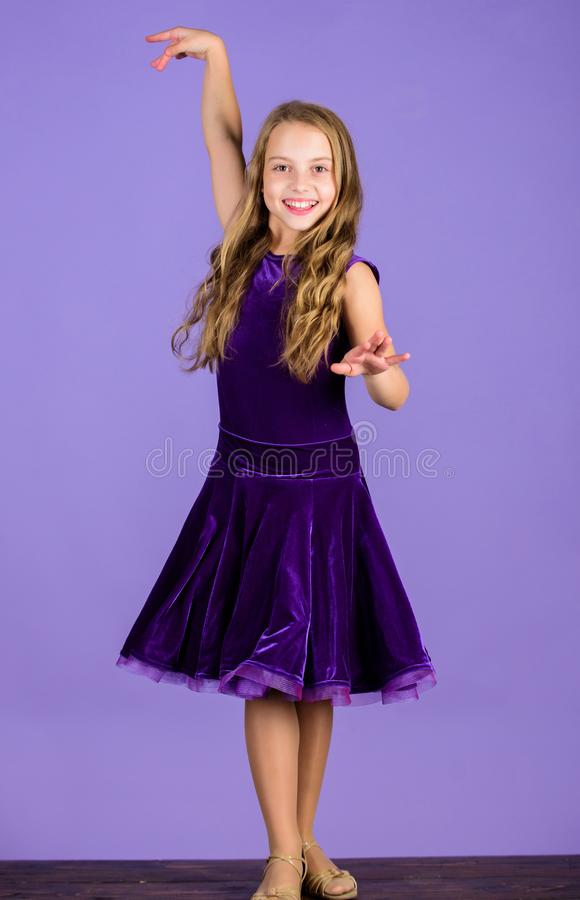 Kid dancer satisfied with concert outfit. Girl cute child wear velvet violet dress. Clothes for ballroom dance. Kids. Fashion. Kid fashionable dress looks royalty free stock images