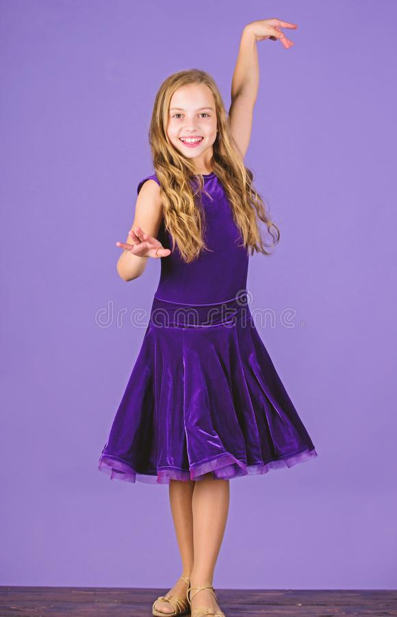 Kid dancer satisfied with concert outfit. Girl cute child wear velvet violet dress. Clothes for ballroom dance. Kids. Fashion. Kid fashionable dress looks royalty free stock photo