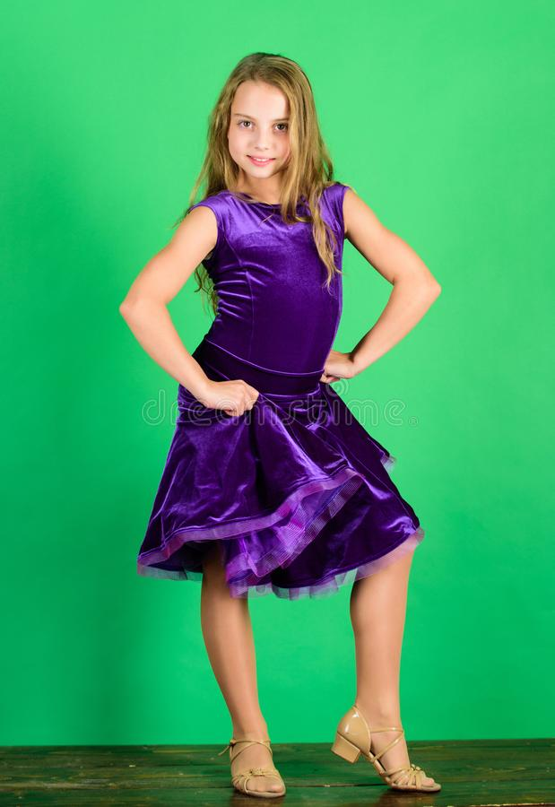 Kid dancer satisfied with concert outfit. Kids fashion. Kid fashionable dress looks adorable. Girl cute child wear. Velvet violet dress. Clothes for ballroom stock photo