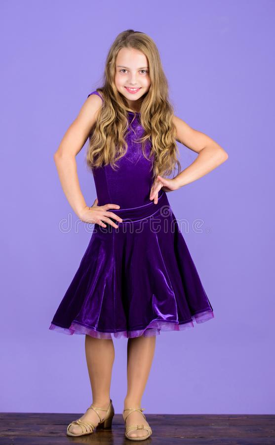 Kid dancer satisfied with concert outfit. Kids fashion. Girl cute child wear velvet violet dress. Clothes for ballroom. Dance. Kid fashionable dress looks royalty free stock images