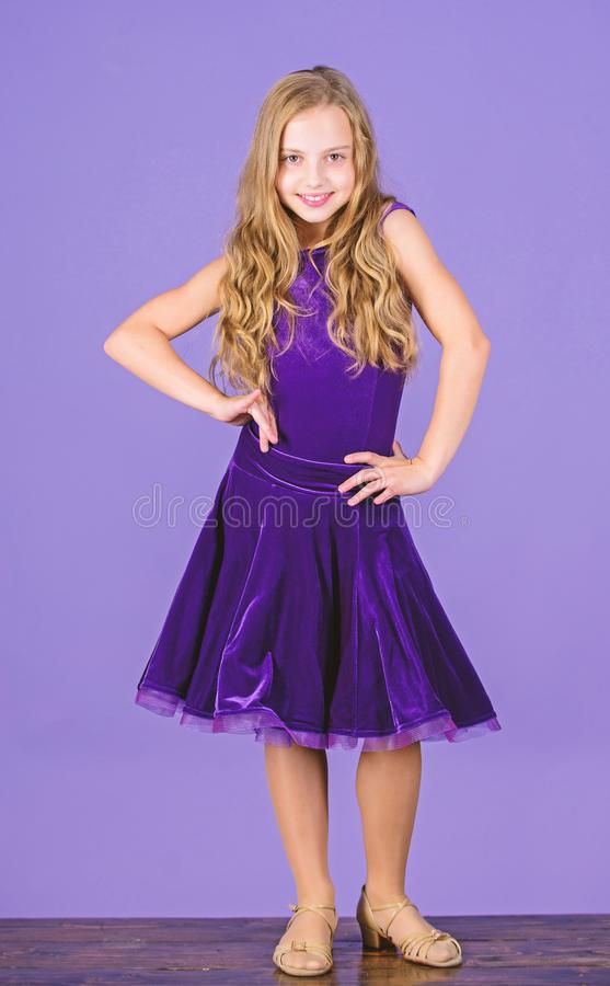 Kid dancer satisfied with concert outfit. Kids fashion. Girl cute child wear velvet violet dress. Clothes for ballroom. Dance. Kid fashionable dress looks stock photos