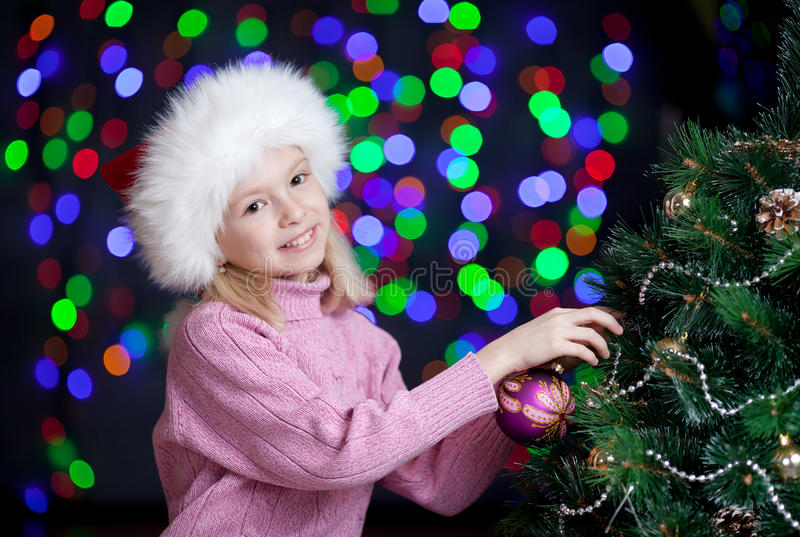 Download Kid Decorating Christmas Tree On Bright Backdrop Stock Photo - Image: 26741228