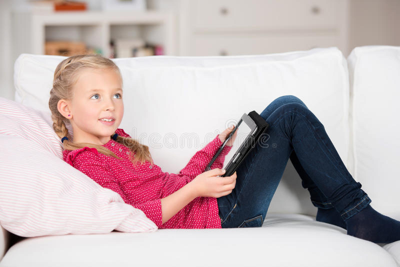 Kid with digital pad lying on sofa royalty free stock images