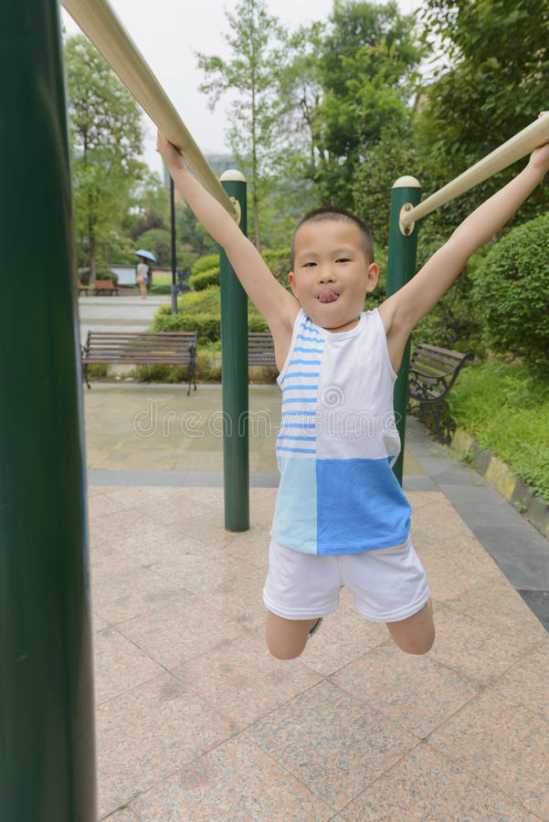 Kid doing exercise. Chinese kid doing exercise hanging on parallel bars in park royalty free stock photography