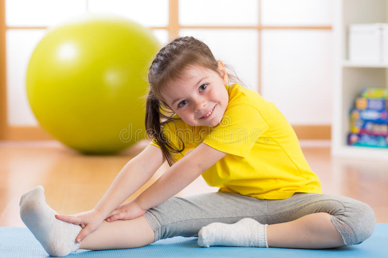 Kid doing fitness exercises. At home in her room stock images