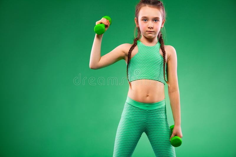 Kid girl doing fitness exercises with dumbbells on green background. Kid doing fitness exercises at home in her room royalty free stock photography