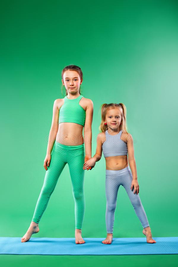 Kid girl doing fitness exercises on green background. Kid doing fitness exercises at home in her room royalty free stock image
