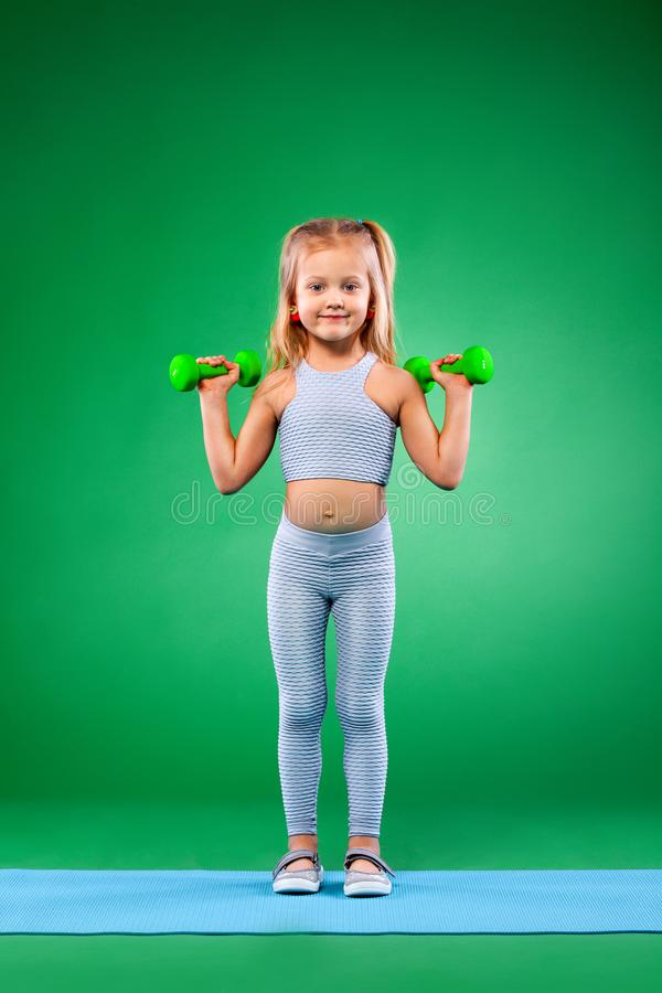 Kid girl doing fitness or yoga exercises with dumbbells isolated on green background. Kid doing fitness exercises at home in her room royalty free stock photo