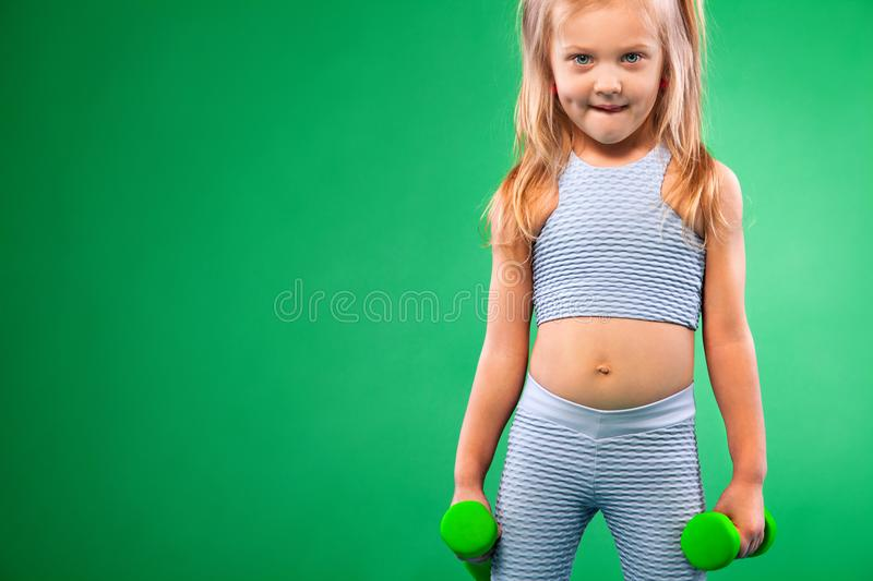 Kid girl doing fitness or yoga exercises with dumbbells isolated on green background. Kid doing fitness exercises at home in her room stock photography