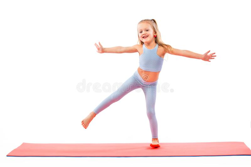 Kid girl doing fitness or yoga exercises isolated on white background. Sport concept. Kid doing fitness exercises at home in her room stock photos