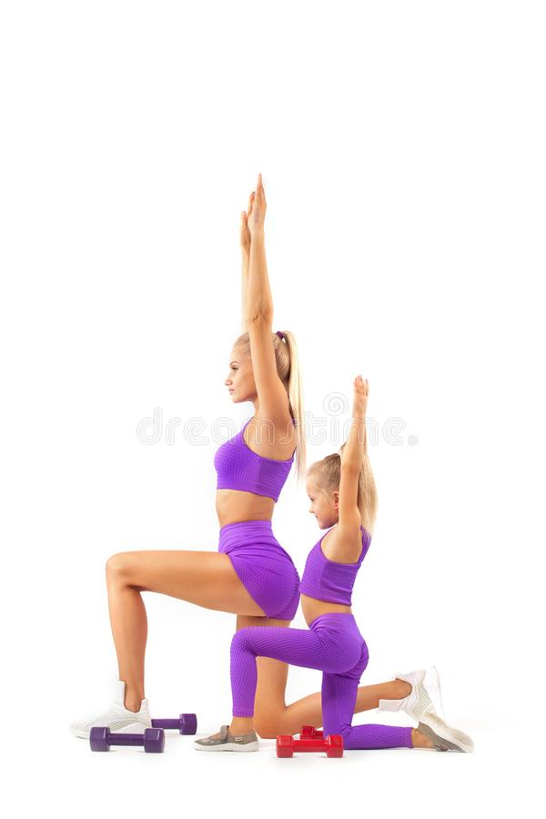 Mother trainer and kid girl doing fitness or yoga exercises with dumbbells on white background. Kid doing fitness exercises at home in her room stock image