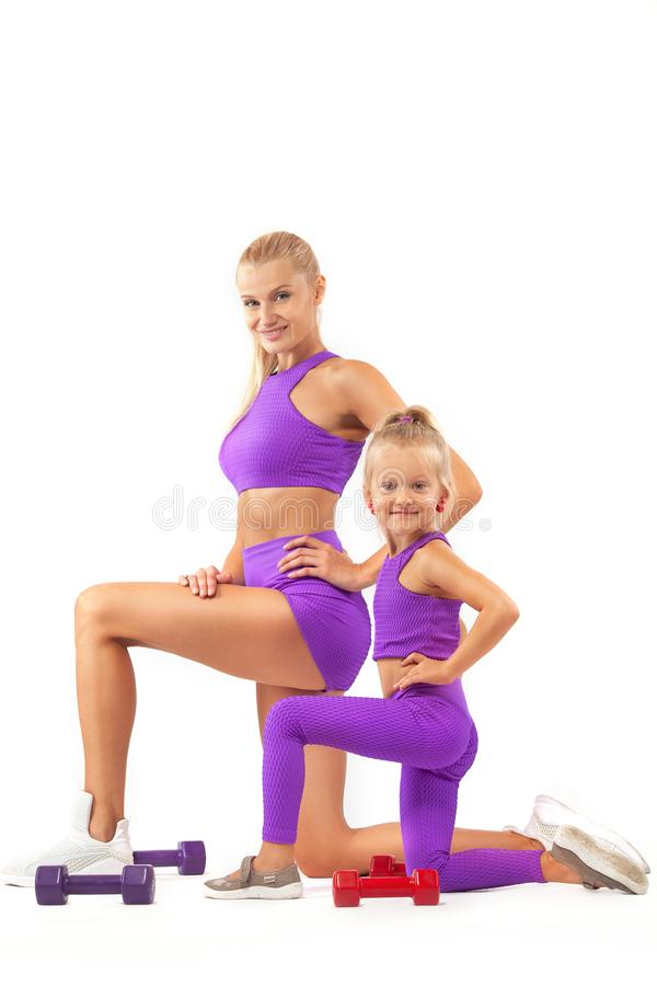 Mother trainer and kid girl doing fitness or yoga exercises with dumbbells on white background. Kid doing fitness exercises at home in her room royalty free stock photo