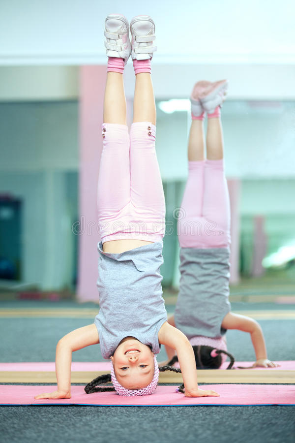 Kid doing fitness exercises. Near mirror stock photography