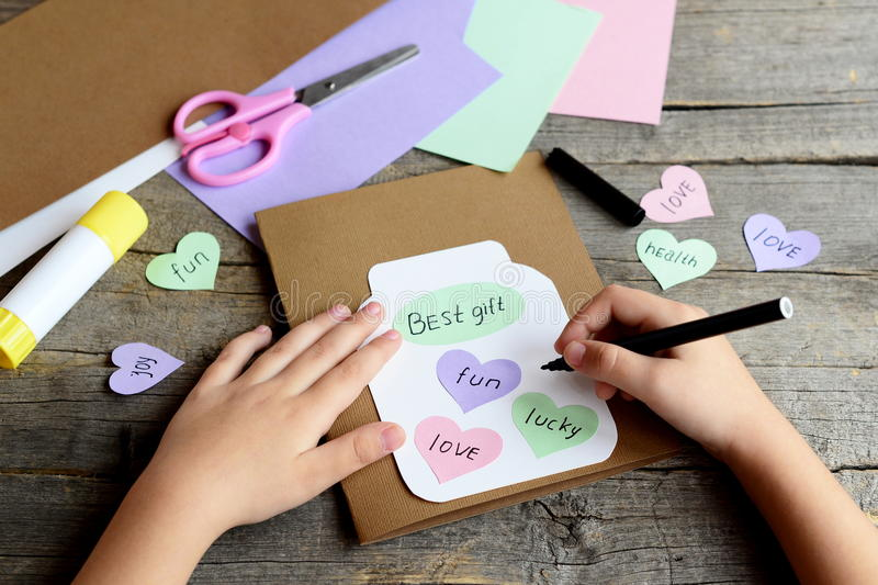 Kid doing a greeting card. Kid holds a black marker in hand and writes wishes. Paper greeting card with jar, hearts and wishes royalty free stock photo