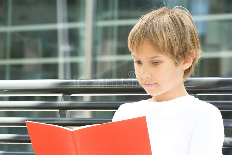 Kid doing homework, reading book textbook outdoors. Child doing homework, reading book textbook outdoors royalty free stock image