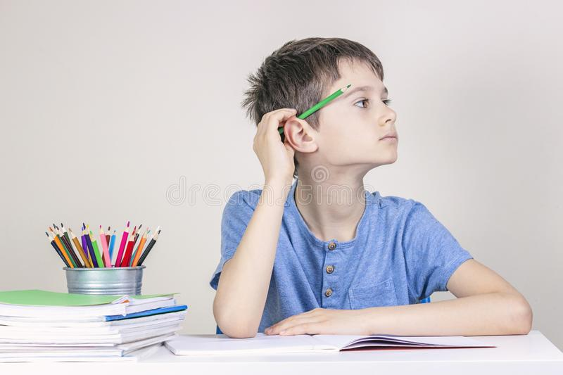 Kid doing homework at the table. Boy with pencil behind his ear thinking or dreaming and looking away royalty free stock photo