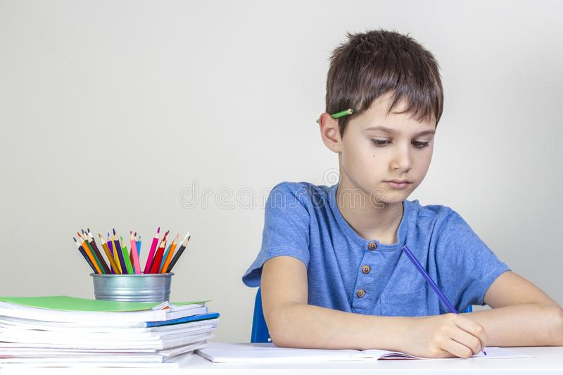 Kid doing homework at the table. Focused boy with pencil behind his ear writing with pencil.  stock image