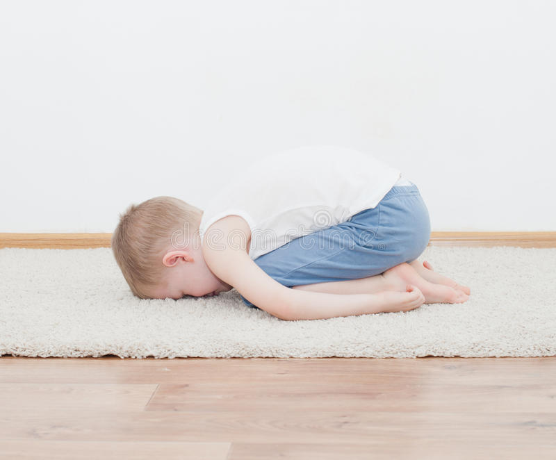 Kid doing yoga relaxing exercise. In his room stock images